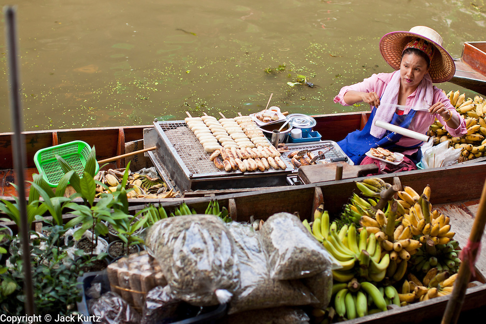 """10 JULY 2011 - DAMNOEN SADUAK, RATCHABURI, THAILAND:  A vendor in the floating market in Damnoen Saduak, Thailand, grills bananas on her boat. The Thai countryside south of Bangkok is crisscrossed with canals, some large enough to accommodate small commercial boats and small barges, some barely large enough for a small canoe. People who live near the canals use them for everything from domestic water to transportation and fishing. Some, like the canals in Amphawa and nearby Damnoensaduak (also spelled Damnoen Saduak) in Rajburi  province (also spelled Ratchaburi) are also relatively famous for their """"floating markets"""" where vendors set up their canoes and boats as floating shops.     PHOTO BY JACK KURTZ"""