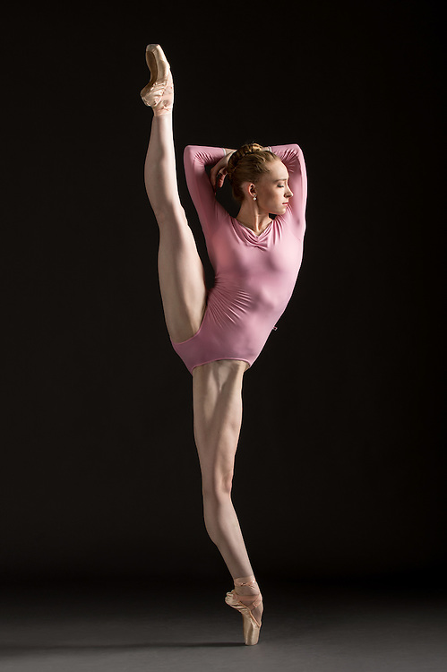 Contemporary ballet female dancer in a pink leotard, Miriam Ernest, in an a la seconde, taken in the photo studio on a black background. Photograph taken in New York City by photographer Rachel Neville.