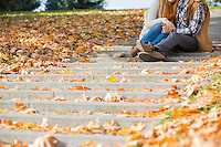 Low section of couple sitting on steps in park during autumn