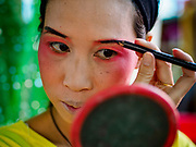 26 AUGUST 2018 - GEORGE TOWN, PENANG, MALAYSIA: A performer puts on her make up before going on stage for a Hokkien style Chinese opera on the Lim Jetty in George Town for the Hungry Ghost Festival. The opera troupe came to George Town from Fujian province in China. The Hungry Ghost Festival is a traditional Buddhist and Taoist festival held in Chinese communities throughout Asia. The Ghost Festival, also called Ghost Day, is on the 15th night of the seventh month (25 August in 2018). During the Hungry Ghost Festival, the deceased are believed to visit the living. In many Chinese communities, there are Chinese operas and puppet shows and elaborate banquets are staged to appease the ghosts.     PHOTO BY JACK KURTZ