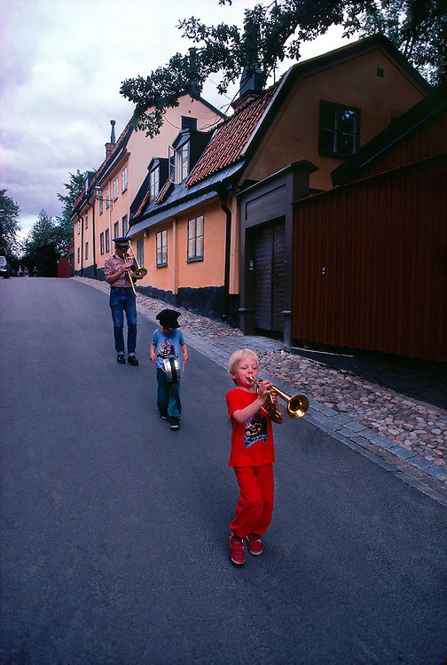 Swedish family parading down street with their musical instruments, Stockholm, Sweden