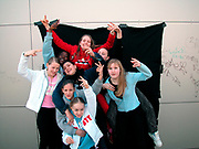 Group of eight girls gesturing to the camera London 2000
