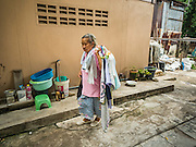 30 JULY 2016 - BANGKOK, THAILAND: A woman brings in her laundry after she washed it in community laundry drying area in the Pom Mahakan Fort slum. The community is known for fireworks, fighting cocks and bird cages. Mahakan Fort was built in 1783 during the reign of Siamese King Rama I. It was one of 14 fortresses designed to protect Bangkok from foreign invaders. Only of two are remaining, the others have been torn down. A community developed in the fort when people started building houses and moving into it during the reign of King Rama V (1868-1910). The land was expropriated by Bangkok city government in 1992, but the people living in the fort refused to move. In 2004 courts ruled against the residents and said the city could take the land. Eviction notices have been posted in the community and people given until April 30 to leave, but most residents have refused to move. Residents think Bangkok city officials will start evictions around August 15, but there has not been any official word from the city.      PHOTO BY JACK KURTZ
