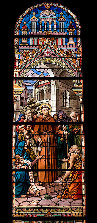 Stained glass image of St. Francis of Assisi giving coins to the poor. (Sam Lucero photo)