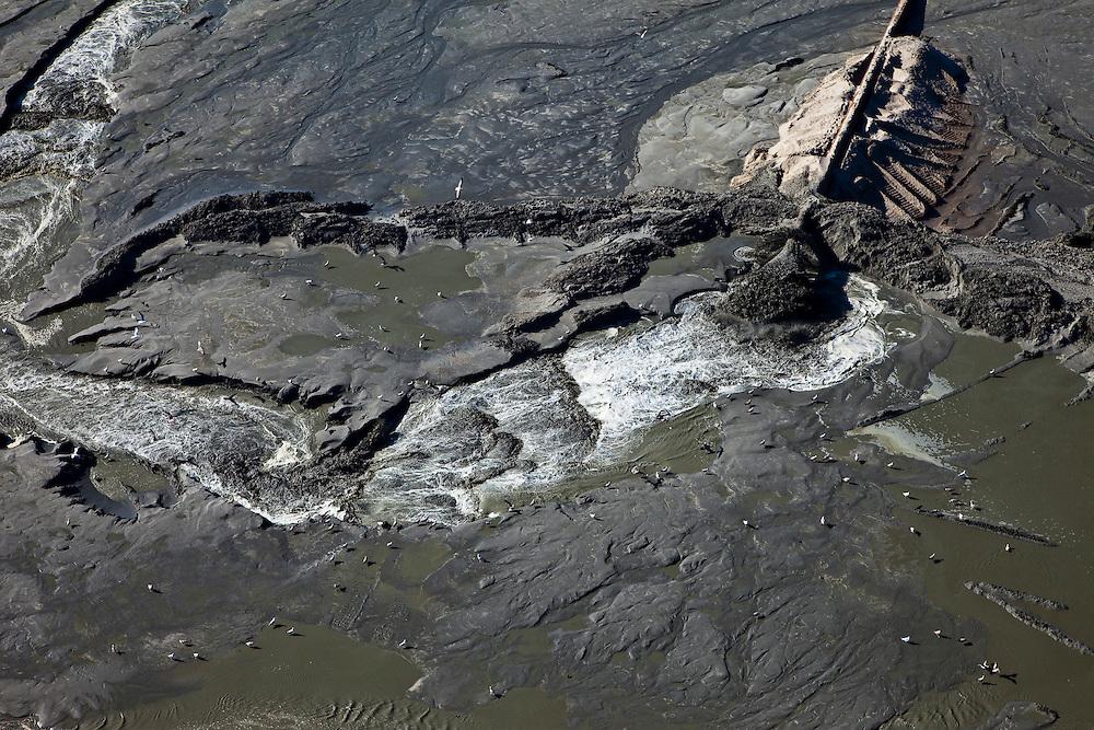 Nederland, Zuid-Holland, Monster, 18-03-2009; Detail van het opspuiten van zand in kader van de versterking van de kust van Delfland tussen Ter Heijde en 's-Gravenzande door middel van zandsuppletie. Omdat het zand hoog op het strand opgespoten moet worden, zijn er dammen aangelegd om het zand tegen te houden, het overtollig water loopt naar opzij terug naar zee. De Delflandse kust is een van de 'Zwakke Schakels' in de zeewering..The coast of Delfland, between Hoek van Holland and The Hague, is been between strengthened by means of sand-supplementation. Bulldozers have made a dams to keep the new sand in place when it is sprayed high on the beach, the surplus of water flows back to the sea. .Swart collectie, luchtfoto (toeslag); Swart Collection, aerial photo (additional fee required); .foto Siebe Swart / photo Siebe Swart