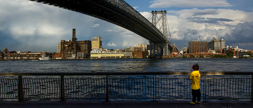 NYC, Williamsburg Bridge, 5-7 year old boy first fishing experience on east river, dramatic sky.