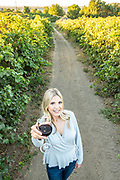 Woman gives a cheers to viewer with glass of red wine at Holeinsky Vineyard and Winery in Buhl, Idaho.