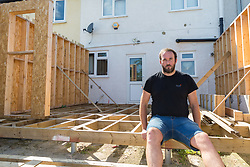 Alan Street sits disconsolately among the timbers of an extension he was having built for his Hornchurch, Essex home, only for the company constructing it to cease trading, leaving him thousands of pounds out of pocket and with planning headaches to solve after the builders failed to seek the proper permissions for the piles on which the structure would stand. Hornchurch, Essex, July 29 2019.