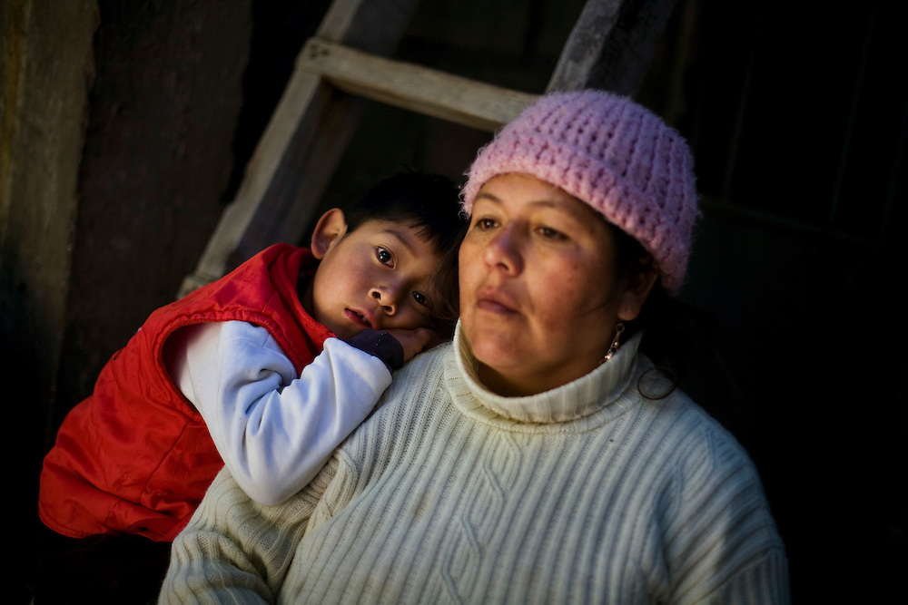 A mother stands with her child, who has severe lead poisoning inside their home in La Oroya Vieja, the part of town closest to the processing plant.
