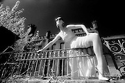 Long white dress one leg over fence with sunglasses - One Woman Show