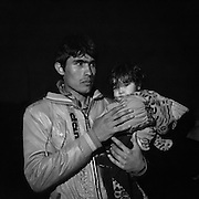 Greece, Chios,<br /> The Odyssey. It Does Not Ends Here 4, <br /> Hands Of My Dad<br /> <br /> Refugees a few minutes after arriving at the coast in Chios, near Karfaz.  <br /> They came from Cesme, Turkey with a dinghy and with fake life jackets at night. Depending on the sea, it takes them between three to five hours to cross the Aegean Sea between Turkey and Greece, depending where they start, its about minimum 8 nautical miles between coast to coast. Refugees from Afghanistan, Iran, Syria and other countries form the near east, made it to Greece by crossing the Aegean Sea with a rubber dinghy.