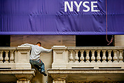 NYSE Stock Exchange the day after the bail-out package was rejected in the House. A NYSE worker does some balancing 15 feet above ground.