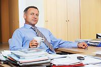 Businessman at desk looking away