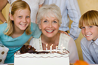 Senior woman with family blowing candles on birthday cake