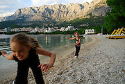 Two children (9 years old and 5 years old) running along beach, with the Biokovo National Park, part of the Dinaric Alps, in the background. Makarska, Croatia