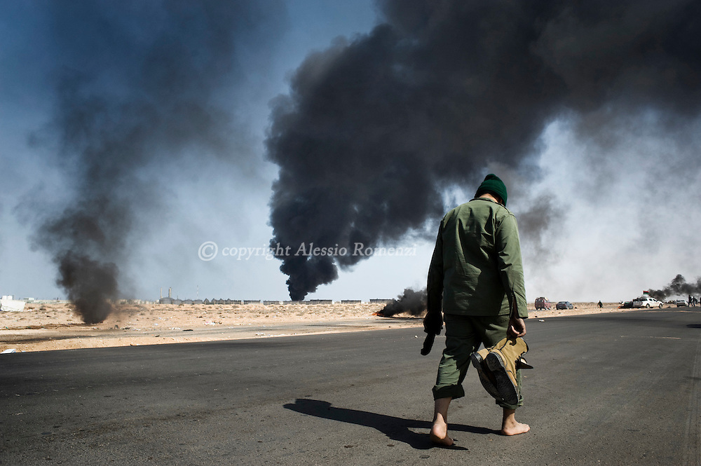 LIBYA, RAS LANUF : Libyan rebel walking on the frontline as smoke from a damaged oil facility darkens the sky on March 11, 2011 in Ras Lanuf, Libya. Government troops loyal to Libyan leader Moammar Gaddafi drove opposition forces out of the strategic oil town, forcing a frantic rebel retreat through the desert.ALESSIO ROMENZI
