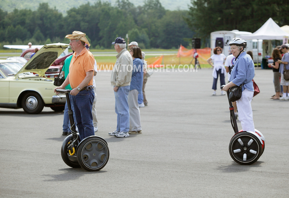 Wurtsboro, NY - An elderly couple riding on Segway Personal Transporters move through a festival at Wurtsboro Airport on Aug. 30, 2009.