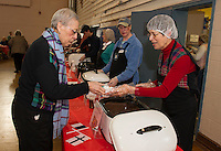 "Elaine Cote serves Brazilian black bean soup to Josephine Estrada during Hands Across the Table's ""Soupathon"" on Sunday evening.  (Karen Bobotas/for the Laconia Daily Sun)"