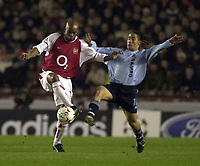 Photo: Greig Cowie<br />Champions League Second Group Stage. Group B Arsenal v Ajax. 18/02/2002<br />Arsenal goalscorer Wiltord holds off a challenge from Ajax's Steven Pienaar