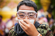 24 NOVEMBER 2012 - BANGKOK, THAILAND:  A man with goggles and breathing mask to offset the effects of tear gas used by Thai riot police during a large anti government, pro-monarchy, protest  on November 24, 2012 in Bangkok, Thailand. The Siam Pitak group, which sponsored the protest, cited alleged government corruption and anti-monarchist elements within the ruling party as grounds for the protest. Police used tear gas and baton charges againt protesters.       PHOTO BY JACK KURTZ