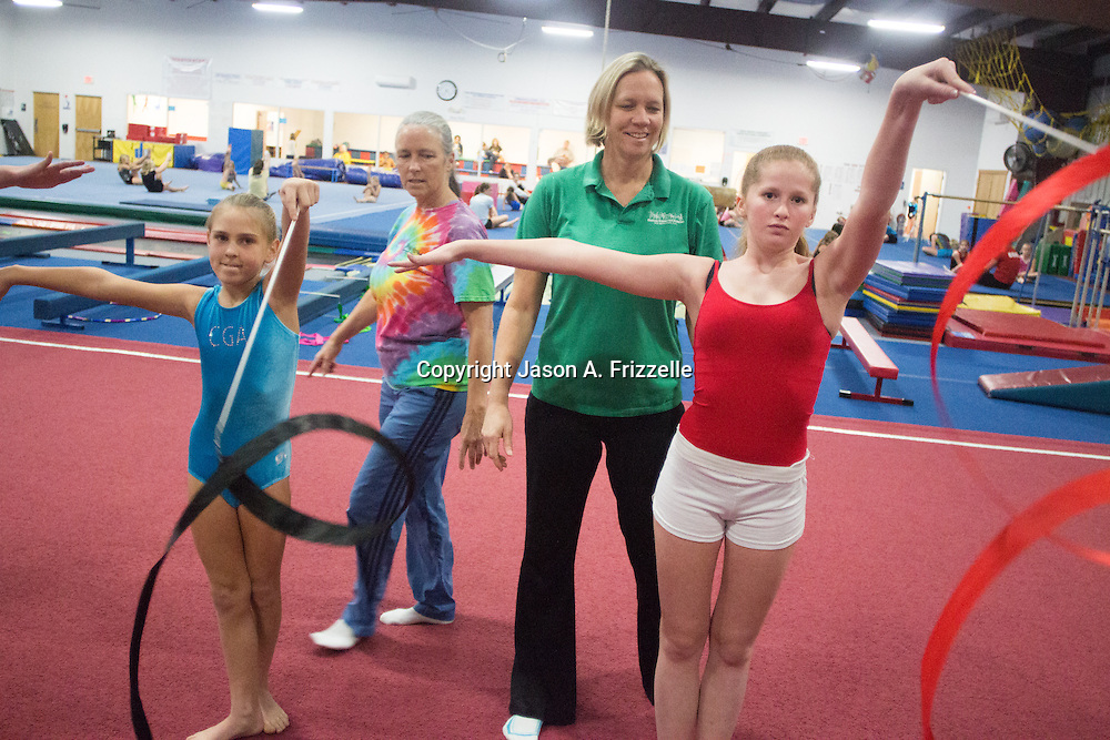 Rebecca Bishop, back-right and Michele Zapple, back-left, owners of Carolina Gymnastics Academy work with Olivia Frederiksen, 10, left, and Mary Andrews, 14 at the academy Tuesday January 21, 2014.  (Jason A. Frizzelle)