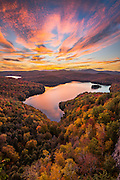 A stunning sunset over a idyllic pond in Northern Vermont surrounded by vibrant fall foliage covered hills.