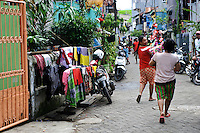 Women walking along the street with decorations in preparation for the Maulid Nabi festival, Makassar, Sulawesi, Indonesia.