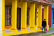 A woman walks past a colorful colonnade style building in Tlacotalpan, Veracruz, Mexico. The tiny town is painted a riot of colors and features well preserved colonial Caribbean architectural style dating from the mid-16th-century.