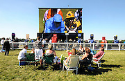 16/06/2010..Members of the public watch a giant TV screen featuring the racing happening behind them at Ascot Racecourse..Over the past 300 years Royal Ascot has established itself as a national institution and the centrepiece of the British social calendar as well as being the ultimate stage for the best racehorses in the world...