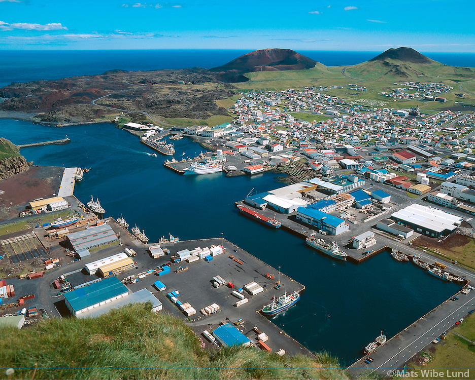 Vestmannaeyjar harbour and town - and both the new volcano Eldfell and lavafiled from 1973 and the old volcano Helgafell. Photo taken from Stori Klif
