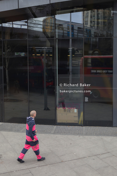 A man wearing a striped onsie looks at his own reflection, on 23rd February 2017, in Elephant & Castle, London, England.