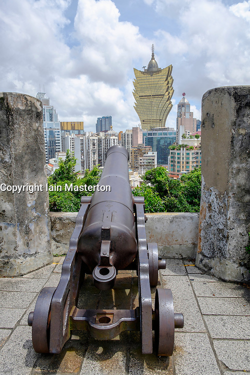 Canon in historic Monte Fort castle with the Grand Lisboa Casino in distance in Macau China