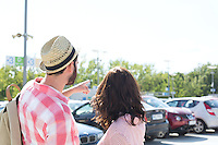 Man showing something to woman on city street against clear sky