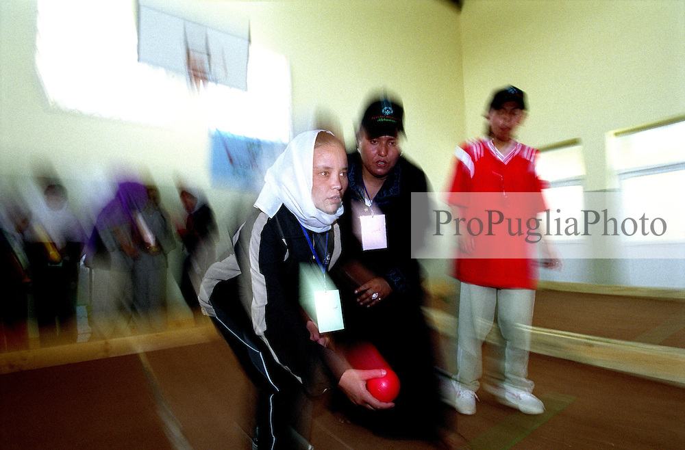 KABUL 24 August 2005..Female athlete wearing a white scarf, throwing a red ball, plays bocce's game at Bagh-e-Zanana...On 23-25 August 2005, Special Olympics Afghanistan held its first national Games at Olympic Stadium in Kabul. More than 300 athletes, including 80 female athletes, experienced a taste of happiness and achievement for the first time in their lives. They competed in athletics, bocce and football (soccer). Because of cultural restrictions, males and females competed at separate venues.