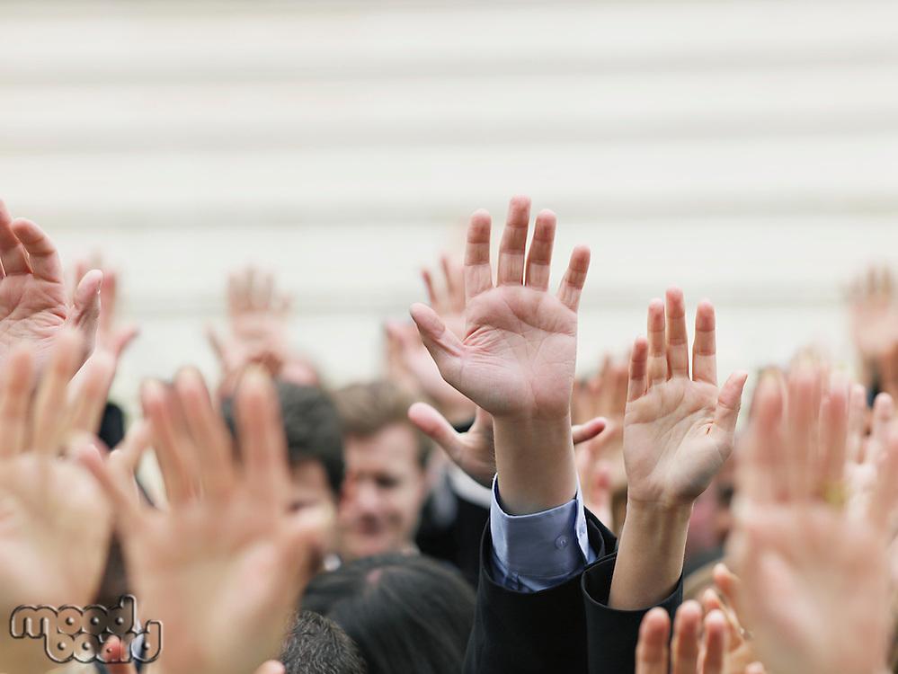 Crowd of people raising hands focus on hands