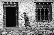 BHUTAN, LAYA VILLAGE, school boy w/ books and boys seen thru window
