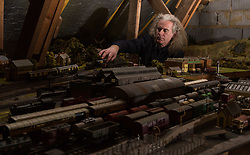 Brothers Simon, 53 and Paul Hurst, 58 have some of their late father's ashes carried around his extensive model railway in the loft of his home. PICTURED: Simon sets the coal wagon carrying his late father Peter's ashes on the tracks. Leeds, Kent, March 15 2018.