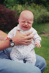 Adult holding crying baby,