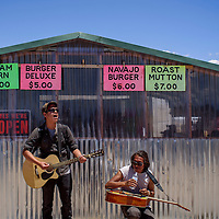 Chad Yazzie sings to the passing crowd while Ted Begay takes a water as the pair perform at the Gallup Flea Market Saturday.