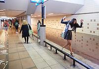 Den Haag , 23 juni 2016 - Een meisje probeert droog over te komen door over de metalen balken te balanceren. (ze redde het uiteindelijk niet).<br /> Mensen proberen door het water in de voetgangerstunnel van het Station Hollands Spoor naar de treinen te komen, door het noodweer in de nacht en ochtend viel zoveel water dat veel laag staande punten onder water liepen.<br /> Foto: Phil Nijhuis