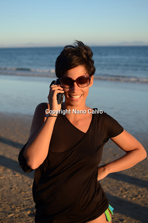 Young attractive woman talks on her mobile phone at the beach