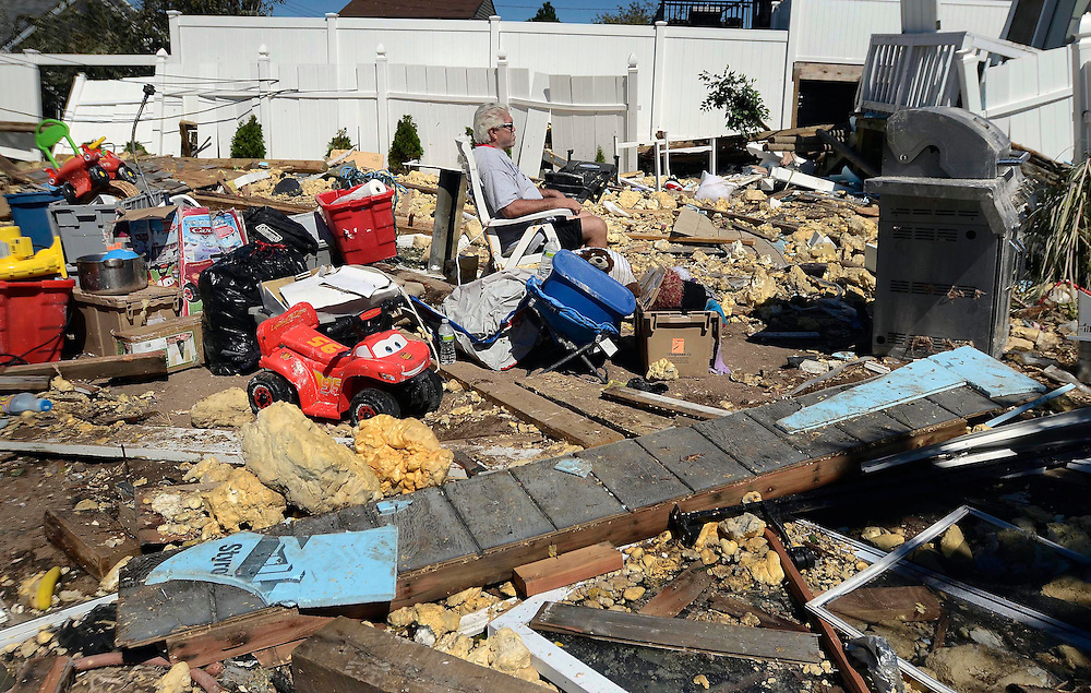 Dave Andrews sits among debris in his friend's yard in the aftermath of Tropical Storm Irene in East Haven, Conn., Monday, Aug. 29, 2011. (AP Photo/Jessica Hill)