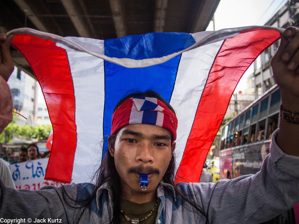 30 NOVEMBER 2013 - BANGKOK, THAILAND:  An anti-government student from Ramkhamhaeng University in Bangkok carries a Thai flag and marches down a Bangkok street Satuday. Political faultlines in Bangkok, the Thai capital, hardened Saturday. Antigovernment factions repeated promises to strike at the heart of Bangkok Sunday and bring down the government while thousands of Red Shirts, who support the government, have come to Bangkok from their base in rural Thailand to defend the government. Prime Minister Yingluck Shinawatra has appealed for calm, but her opponents have rejected all requests for negotiations saying the only acceptable outcome is the eradication of the government.       PHOTO BY JACK KURTZ