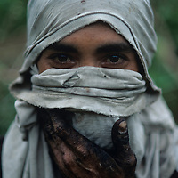 Philippines, Negros Island, Portrait of sugarcane cutter with face and hands covered in black soot while burning fields
