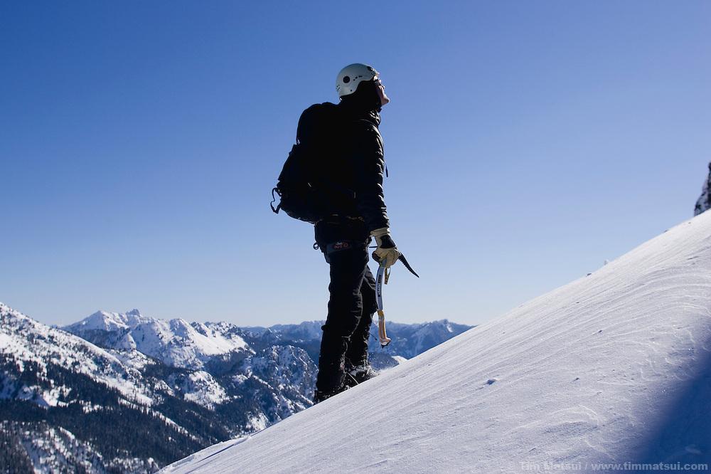 A caucasian man ice climbs in the winter on Chair Peak near Snoqualmie Pass, Washington.