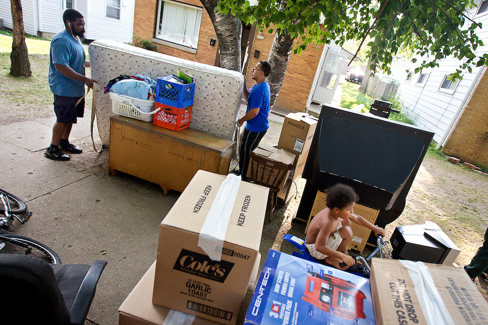 MILWAUKEE, WI — AUGUST 8, 2014: Harry Woods and John Campbell with Eagle Moving and Storage Company removes a bed from 4350 88th Avenue on the North Side of Milwaukee during a tenant eviction.