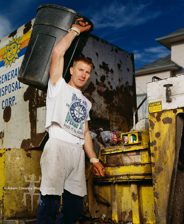 Sanitation worker holding garbage can, portrait