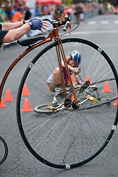 A cyclist participating on a penny-farting bicycles crashes to the ground as she competes in a Lenape Scorcher vintage bike race, held ahead of the September 11, 2016 Bucks County Classic, in Doylestown PA.