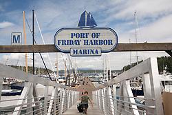 United States, Washington, San Juan Island, Friday Harbor. boy wheeling suitcase up ramp at the Port of Friday Harbor.  MR