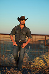 hot cowboy leaning on a fence at sunset